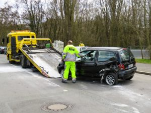 Accident car being pulled onto a flatbed tow truck